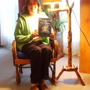Helen, beside the same Diamond Willow lamp, holds a copy of Diamond Willow
