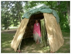 Gretchen Spenn inside the wiikiaami made by Myaamia children and adults at a summer language and culture program in Kekionga/Fort Wayne. in 2011